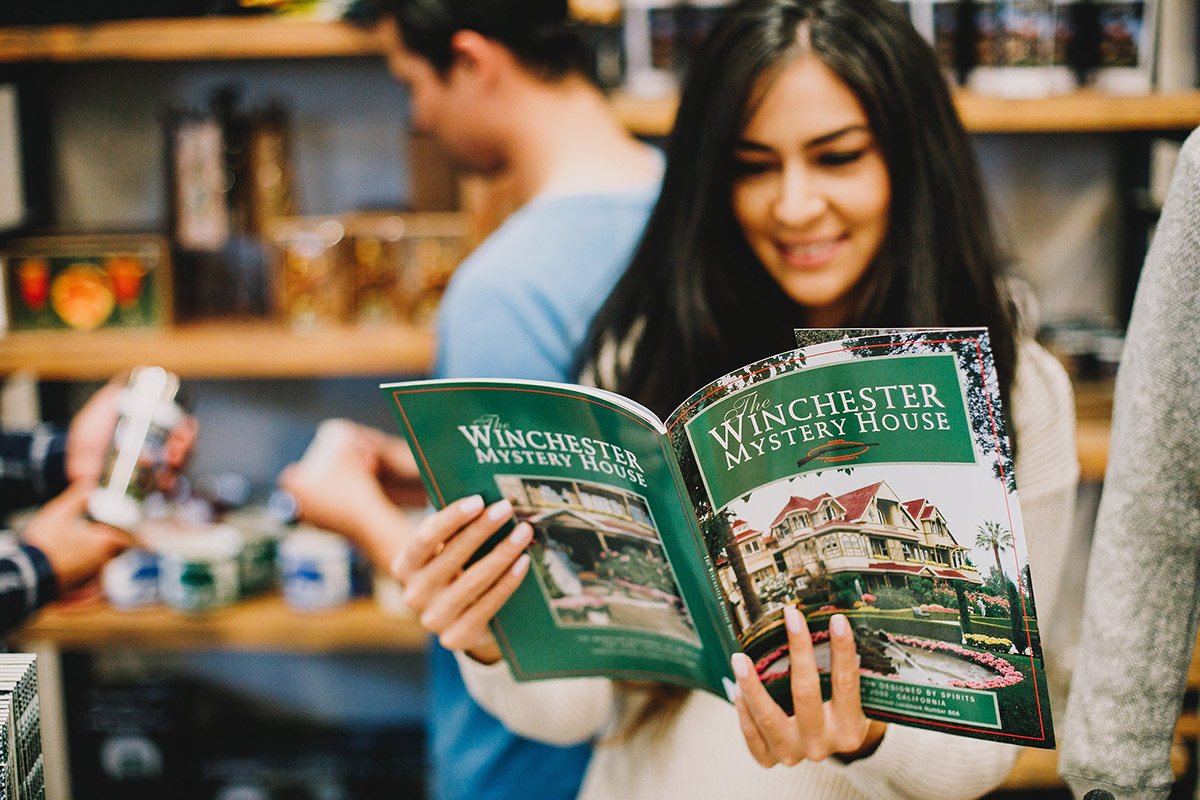 woman reading book on the winchester mystery house