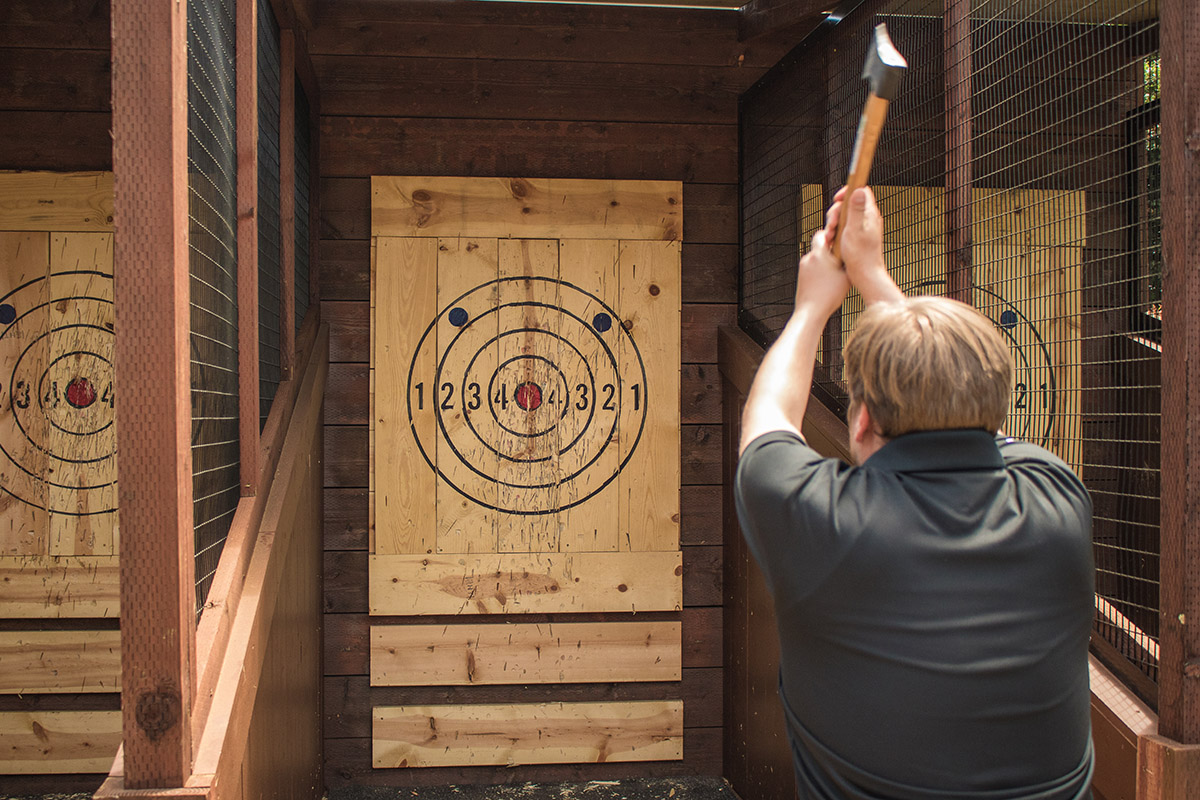 axe throwing coach showing how to throw an axe at the target